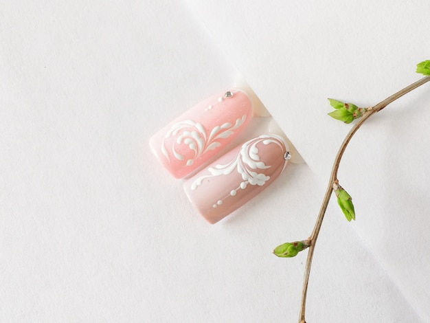 Spring manicure. tips with pink monogram design on a white table.