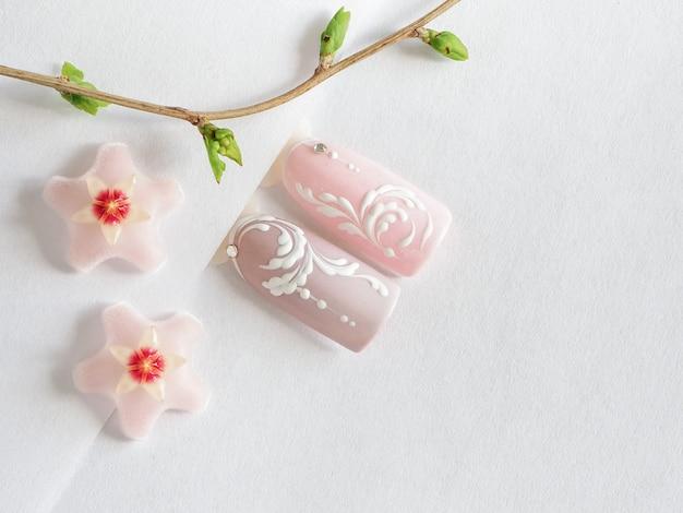 春のマニキュア。白いテーブルに春の花のデザインのヒント