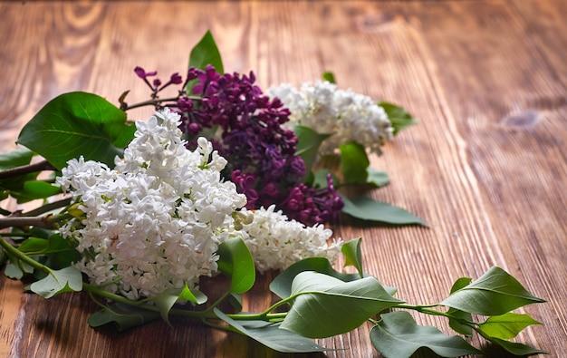 Весенние майские цветы. белые и фиолетовые цветки сирени на деревянном взгляде столешницы.
