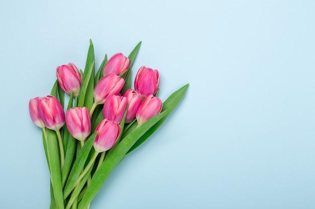 Весенний макет с розовыми тюльпанами на синем фоне. концепция пасхи. скопируйте пространство. вид сверху - изображение