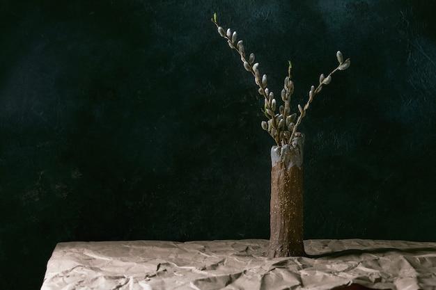 Натюрморт весеннего настроения с ветвями цветущей ивы в керамической вазе на столе с мятой крафт-бумагой.