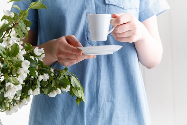 Spring morning, the girl drinks coffee with a bouquet of spring flowers in a vase