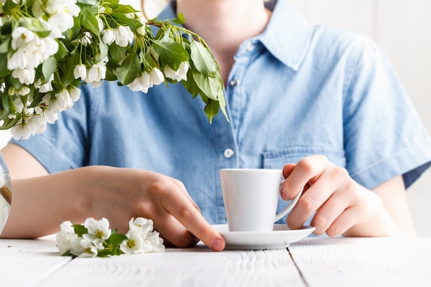 Spring morning, the girl drinks coffee with a bouquet of spring flowers in a vase Premium Photo