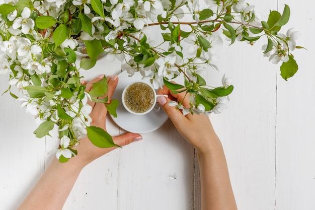 春の朝、女の子は花瓶に春の花の花束とコーヒーを飲む