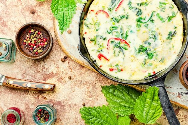 鉄鍋に新鮮なハーブを詰めた春のオムレツ。