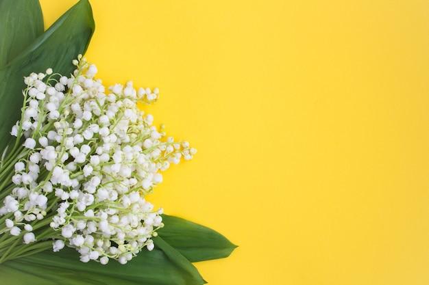 봄 또는 여름 배경입니다. 노란색 배경에 은방울꽃 꽃다발입니다. 상위 뷰입니다. 공간 복사입니다. 봄 꽃 개념입니다.