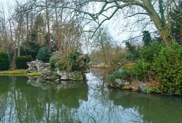 Весенний парк с прудом и отражением деревьев на поверхности воды