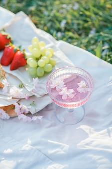 자연 속에서 봄 피크닉. 사쿠라 꽃, 고리 버들 가방, 모자, 이탈리아어와 함께 핑크 샴페인 한잔. 포도주. 봄.