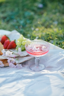 Spring picnic in nature. a glass of pink champagne with sakura flowers, a wicker bag, a hat, italian. wine. spring.