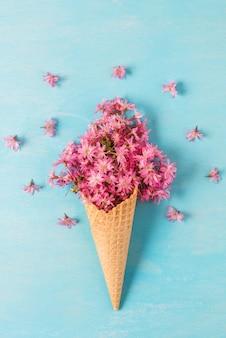 와플 콘에 봄 분홍색 벚꽃 꽃이 만발한 꽃. 최소한의 봄 개념. 수직 방향