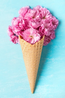 Spring pink cherry blossoming flowers in waffle cone on blue background. minimal spring concept. flat lay. top view
