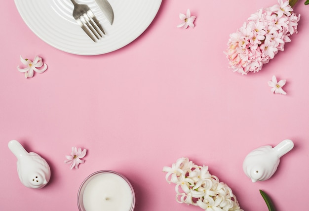 Spring pink flat lay. white table setting and hyacinths flowers