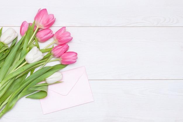 春のピンクのチューリップ、白い木製の背景の空の紙カード。母の、女性の日のコンセプトです。フラット横たわっていた、スペースをコピーします。