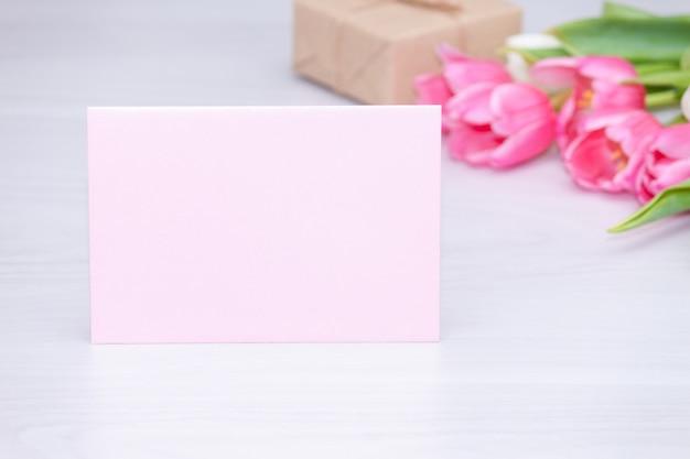春のピンクのチューリップ、ギフトボックス、空の紙カード。母の日コンセプト。