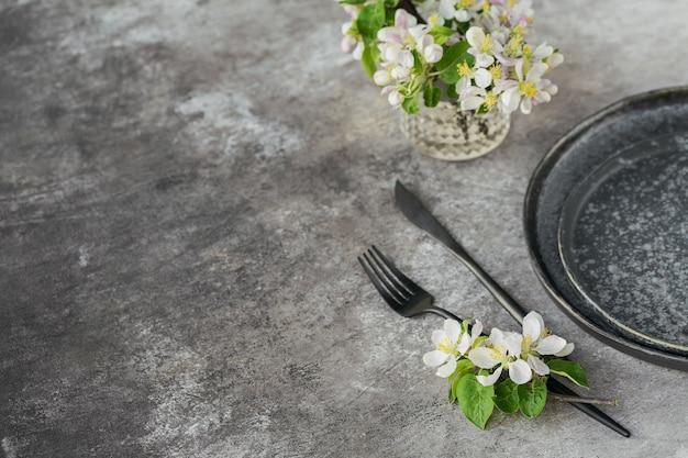 회색 테이블에 꽃이 만발한 사과 나무 가지와 꽃이 있는 봄 장소 테이블 설정. 프로방스 스타일의 휴일 장식입니다. 낭만적인 저녁 식사. 텍스트 복사 공간이 있는 오버헤드