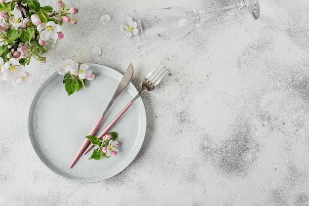 밝은 테이블에 꽃이 만발한 사과 나무 가지와 꽃이 있는 봄 장소 테이블 설정. 프로방스 스타일의 휴일 장식입니다. 낭만적인 저녁 식사. 텍스트 복사 공간이 있는 오버헤드