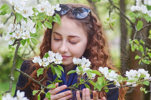 Spring portrait of a beautiful woman smelling magnolia flower