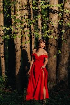 森の中の公園を歩いている長い髪の長い赤いドレスを着て笑っている女の子の春の肖像画