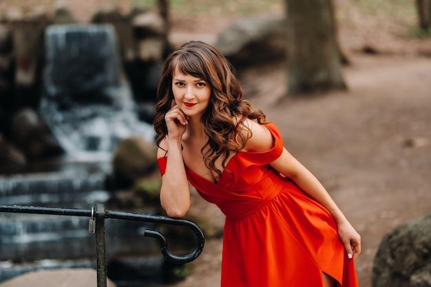 Весенний портрет смеющейся девушки в длинном красном платье с длинными волосами гуляет в парке в лесу