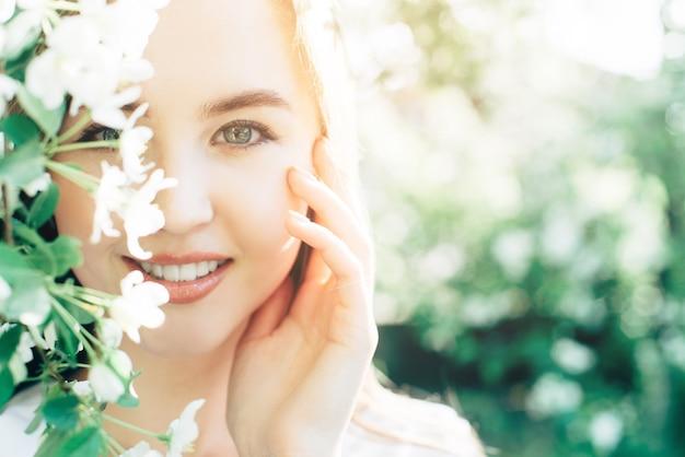 開花のリンゴの木とテキストのための場所を持つ若い女性の春の肖像画。