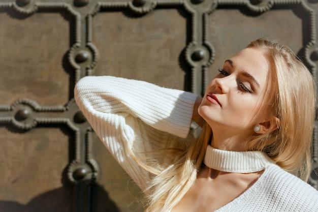 金属製の錬鉄製の門の近くでポーズをとる自然な化粧と完璧な肌を持つ若いモデルの春の肖像画。テキスト用のスペース