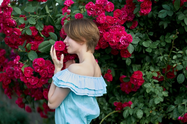 Spring. portrait pretty young woman wearing trendy blue light dress smelling blooming roses in the garden. outdoor.