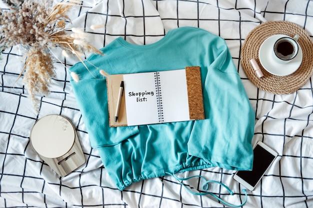 봄 리뉴얼, 판매, 쇼핑. 침대에 스타일 액세서리가 있는 열린 메모장에 있는 옷 쇼핑 목록. 옷장 쇼핑 목록.