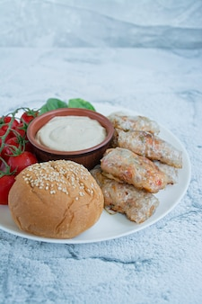 Spring roll with meat and vegetables served on a white dish with sauce.