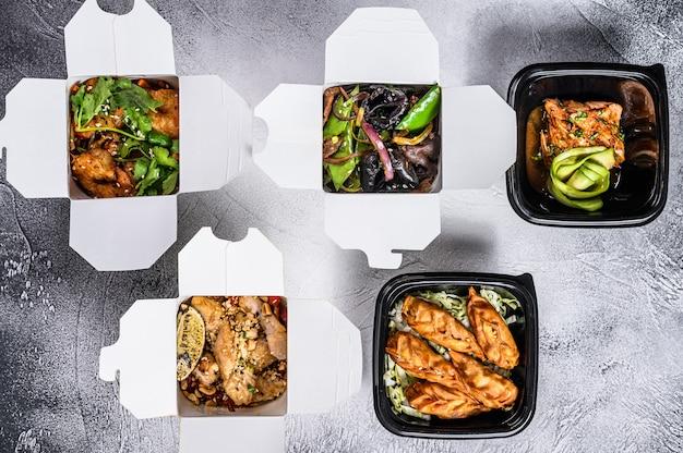 テイクアウェイボックスにある春巻き、餃子、餃子、中華麺。ヘルシーなランチ。有機食品を取りに行きます。白色の背景。上面図