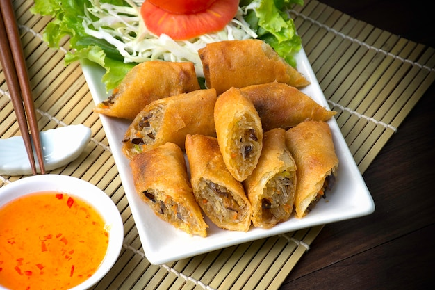 Spring rolls. on white dish in the kitchen / wood and bamboo background /selective focus image