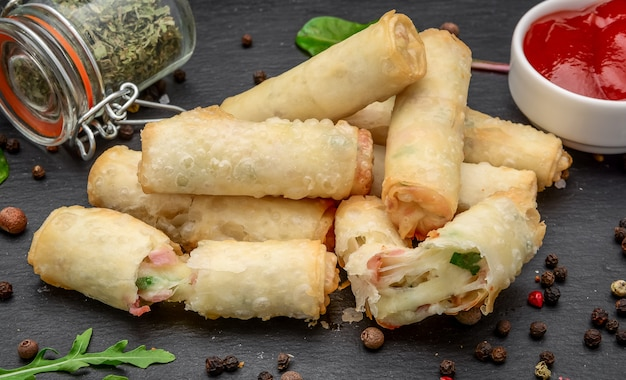 Spring rolls with cheese and ham, on a black stone board. restaurant