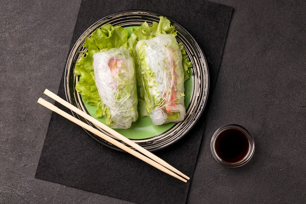 Spring rolls with chopsticks on green plate next to a gray sauce on black