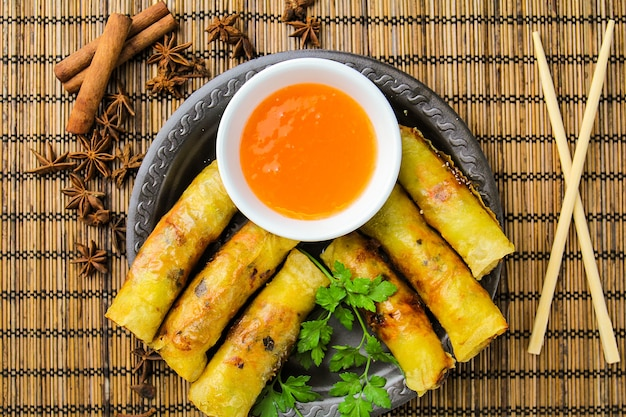 Spring rolls with sweet sauce on black plate