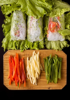 Spring rolls with vegetables on black. near the ingredients of chopped pepper