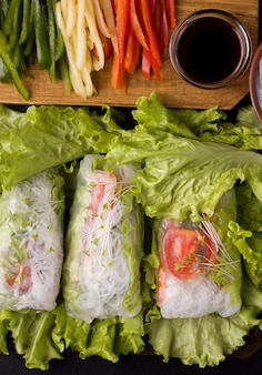 Spring rolls with vegetables on black.
