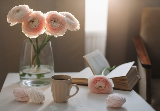 Spring romantic still life with flowers, coffee cup, a book and marshmallows