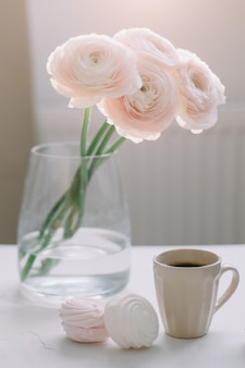 Spring romantic still life with flowers, coffee cup and marshmallow