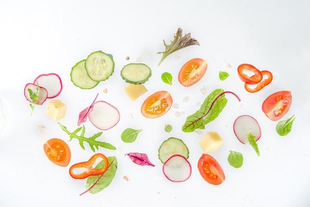 春のサラダ材料のコンセプト。白い背景の上の健康食品。野菜、トマト、ピーマン、緑の葉。フラットレイ、上面図、コピースペース