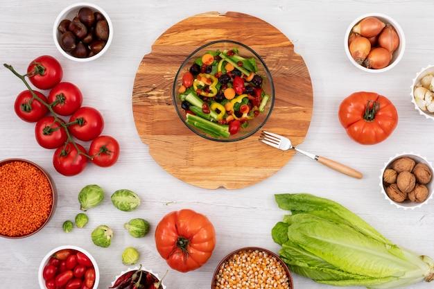 さまざまな新鮮な野菜に囲まれた木の板の春サラダ