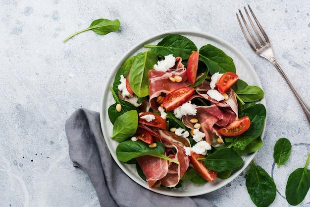 오래된 콘크리트 회색 배경의 단순한 세라믹 접시에 시금치, 체리 토마토, 모짜렐라, 잣, 올리브 오일을 곁들인 햄을 곁들인 스프링 샐러드