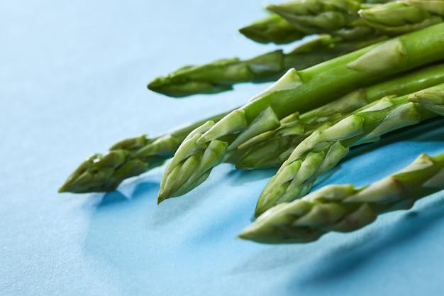 봄 시즌 - 파란색 배경에 신선한 녹색 아스파라거스. 개념 건강한 깨끗한 식사. 플랫 레이