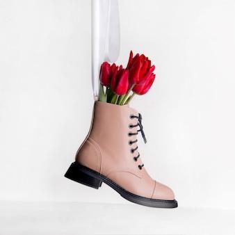 春の靴のコンセプト。白い背景の上の赤いチューリップの花とベージュの靴