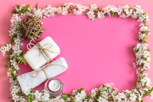 Spring spa ancora in vita sul muro rosa isolato con fiori primaverili