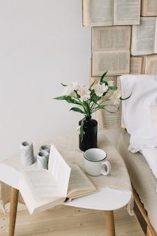 春の静物。ベッドでの朝食。白い寝室。甘い家。本、花、コーヒーカップ。フラットレイ