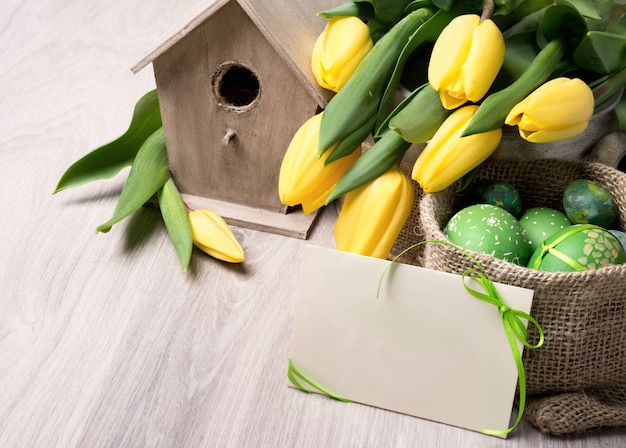 Spring still life decorations with bird house, yellow tulips, easter eggs, text space on paper card