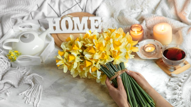 Весенний натюрморт с чашкой чая и цветами. светлый фон, цветущий и уютный дом.