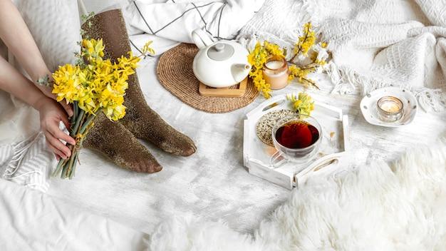 一杯のお茶と黄色い花のある春の静物。ライトテーブル、咲く居心地の良い家。
