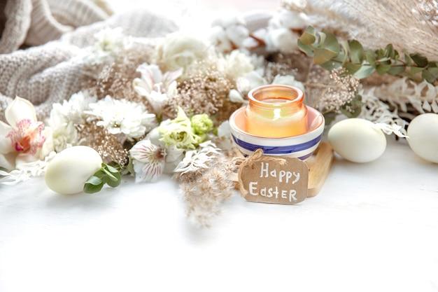 Весенний натюрморт с пасхальными яйцами, зажженными свечами в кулоне и цветами на фоне деталей декора. концепция праздника пасхи.
