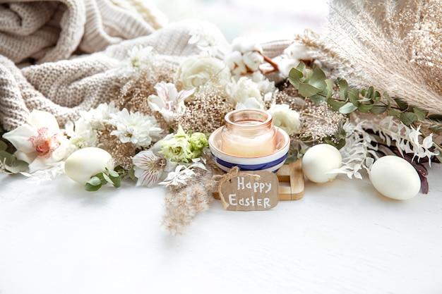 Весенний натюрморт с пасхальными яйцами, свечами в кулоне и цветами на фоне деталей декора. концепция праздника пасхи.