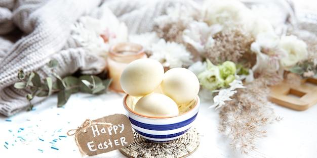 Весенний натюрморт с пасхальными яйцами в красивом блюдце на фоне деталей декора. концепция праздника пасхи.